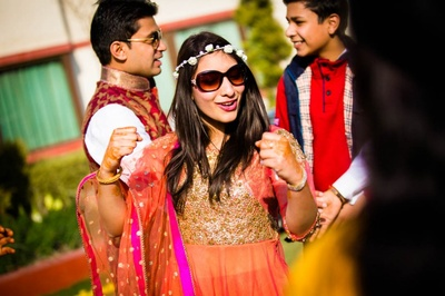 Dressed in an orange net and golden embroidered kurti for an outdoor mehendi ceremony