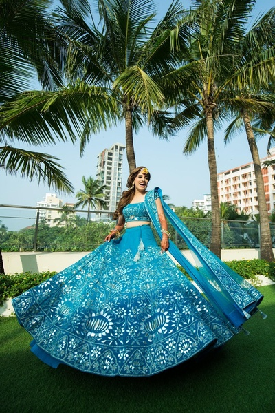 The bride looks scintillating in this blingy blue and silver lehenga, paired with floral jewellery.