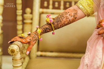 Bride wearing mehendi showing pff her mehendi design