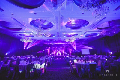 The wedding reception venue decorated with blue lights .