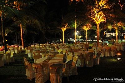 Clustered table chair seating arrangement with white chair cover and gold tie backs