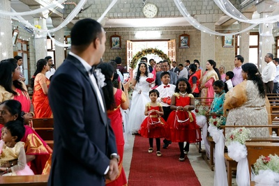 Flower girls and page boy carrying flowers and wedding rings, followed by the bride and her father