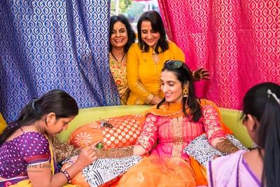 Dressed in orange and pink anarkali for her bridal mehendi at Gold Palace, Kukas, Jaipur