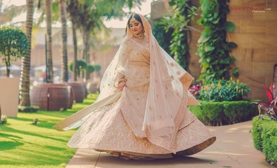 Emma twirling in her ivory and peach lehenga before the wedding function