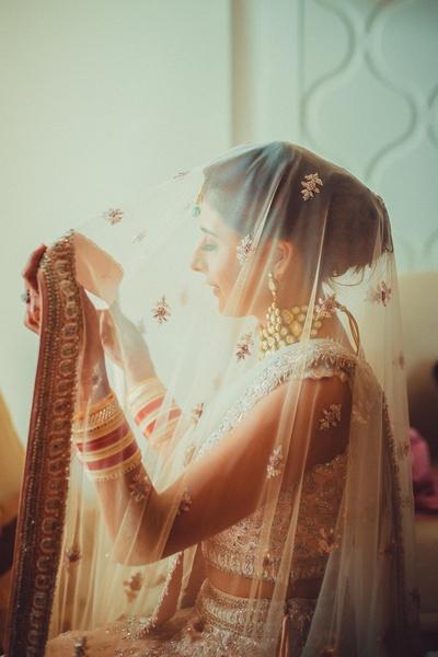 The stunning bride dressed in a pastel bridal lehenga.