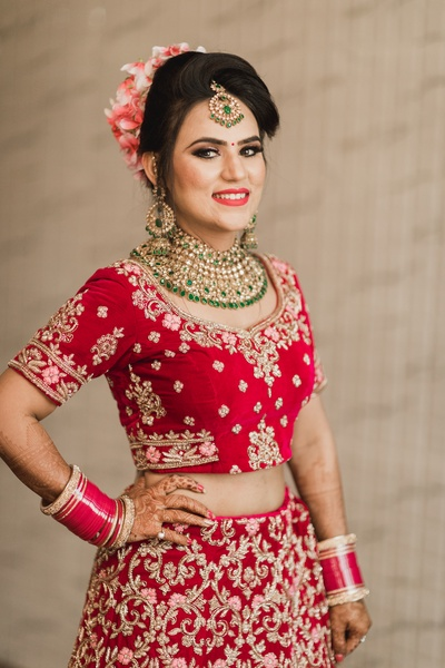 The bride looks gorgeous in this red lehenga and green and gold jewellery.