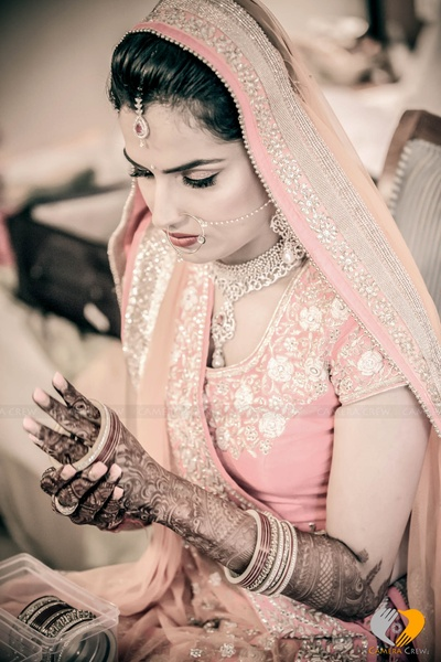 Beautified with chooda set and hoop nose ring the bride is ready to embrace the wedding rituals