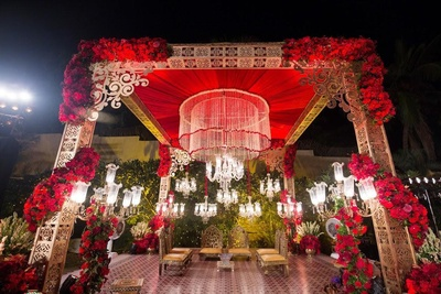 The wedding mandap flaunted vintage crystal chandeliers, gold ornate pillars bedecked with roses and a magnificent floral chandelier.