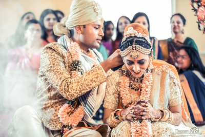 A happy moment for the bride, while her groom puts on the sacred mangalsutra around her neck.