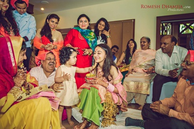 Haldi function in process with a little girl putting haldi on the bride