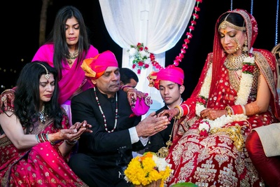 Red bridal lehenga by Sabyasachi styled with majestic polki studded necklace set and glam bridal makeup by Asha Hariharan