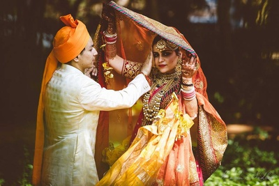 Orange, pink and red wedding lehenga embellished with gota patti work styled with layers of gold jadau bridal jewellery