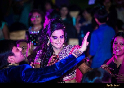 Enjoying the Sangeet ceremony dressed in pink and purple attire