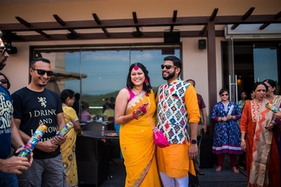 the bride in a pink and yellow saree and the groom in yellow kurta with multicoloured jacket at the haldi