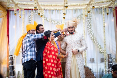 The bride's brothers pulling the groom's ear as part of a tradition.