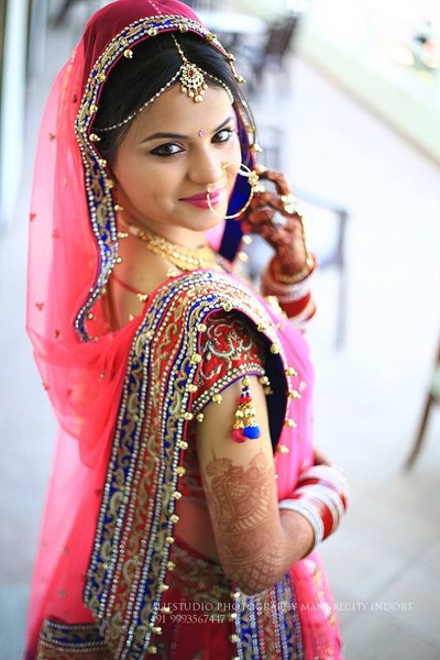 Blush pink wedding lehenga embellished with stones, beads and navy blue and red laces