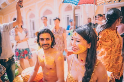 Bride wearing gold tasselled bralette with a rajasthani print wrap around skirt and her hair in a loose braid.