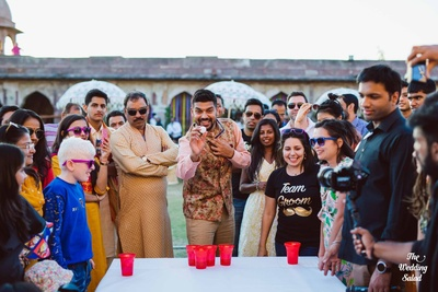 The groom playing beer pong