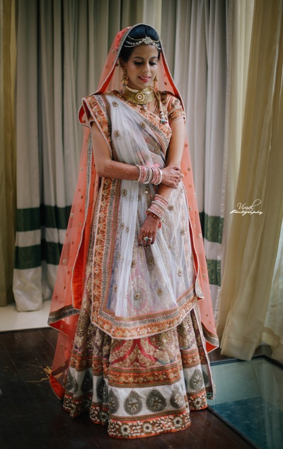 Bride wearing pastel orange and white color bridal lehenga styled elegantly with minimal makeup and jewellery for the wedding day .