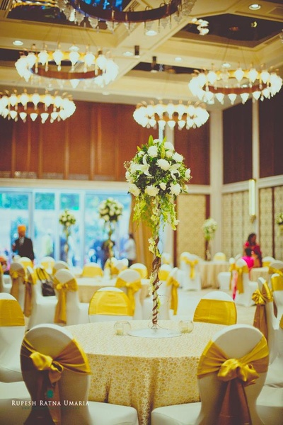 White and gold tie backs, printed table covers and floral topiary standies as centerpieces