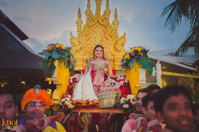 Bride being escorted to the wedding venue on a high-rise palki