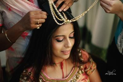 Bride wearing beautiful kundan maang tikka with strings for her wedding.