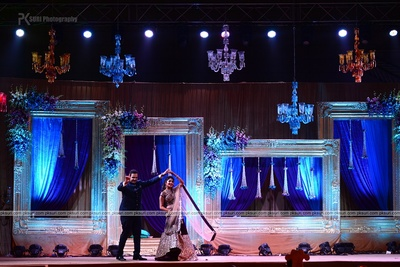 Grand stage decoration with live size frames, crystal chandelier and clustered flower arrangement