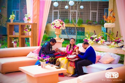 Outdoor mehndi ceremony set up in hues of pink and peach with fresh flowers, drapes and wooden structures