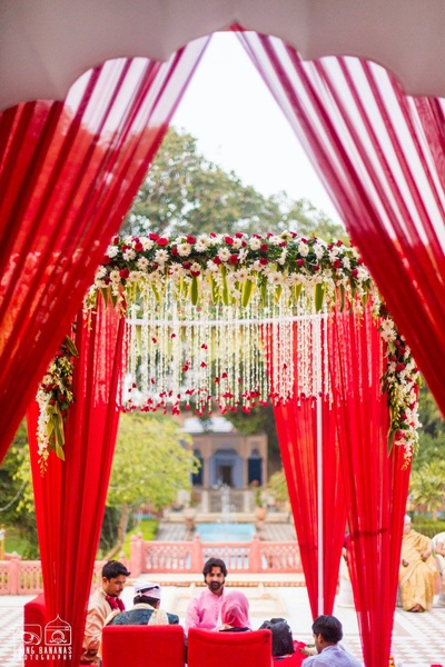 Mandap decorated with bright red drapes and fresh white and red flowers
