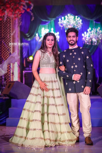 the bride in a mint green lehenga and the groom in navy blue bandhgala for their engagement cereomony