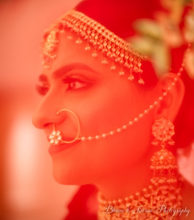 A dramatic shot of the bride behind her red veil.