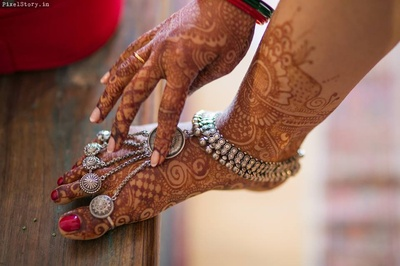 Mehendi feet beautified with silver adornments for the wedding day.