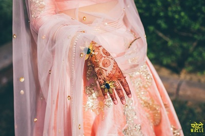 Pastel baby pink silk lehenga with silver and gold zari work for Mehendi ceremony.