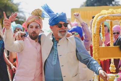 Father of the bride and the groom dancing together in the baraat