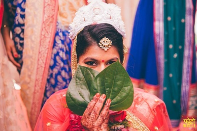 Bride's face covered with betel leaves for the subho dristi ceremony.