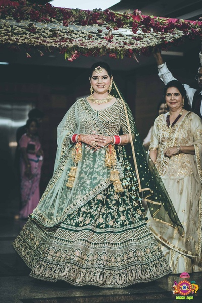 bridal entry under the floral chadar in her green wedding lehenga