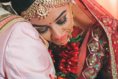 Candid capture of the bride in her red wedding lehenga and soft makeup with a bronze smokey eye