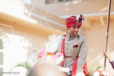 Dressed in a beige textured sherwani with 3D button details with feather topped Kalgi and pocket square