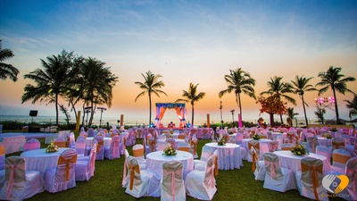 Outdoor wedding decor ideas. Floral table centerpieces, pink halogen lights and coral and pink bow style tie backs