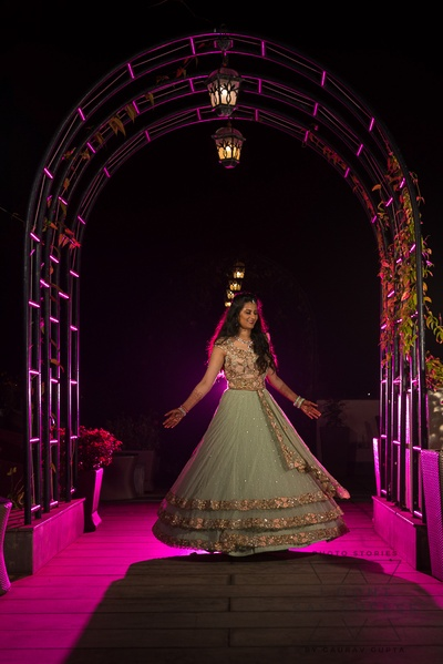 the bride twirling in a mint green and peach lehenga  at her sangeet ceremony
