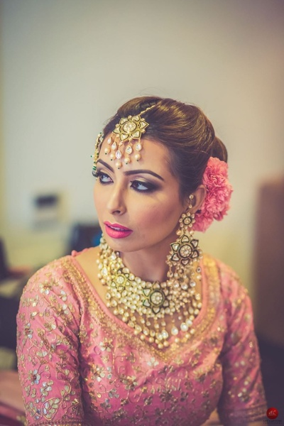 Traditional lehenga worn by the bride perfectly compliments the contrast kundan and green jewellery without looking too monotone