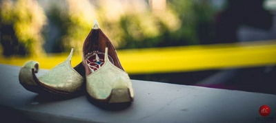 Traditional gold jutis for the groom with a red and blue sole