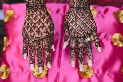 Hands filled with intricate bridal mehendi.