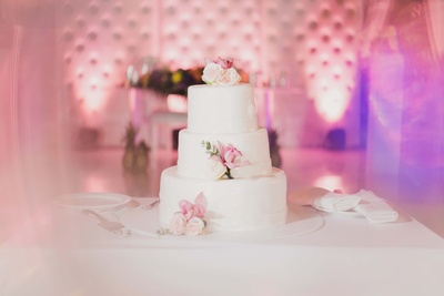 Cake decor for the wedding reception set by the all white theme with floral cake toppers