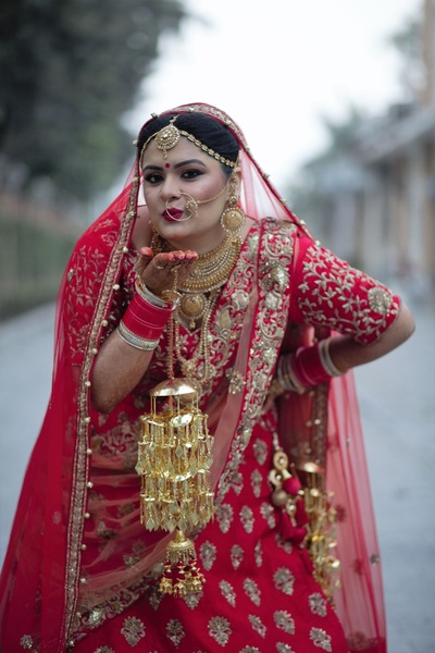 Dressed up in a regal red lehenga and gold kaleere for the wedding ceremony.