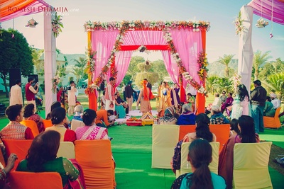 Wedding mandap decorated with colorful flowers and white and pink drapes for the hindu wedding ceremony.