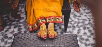 Feet covered in haldi paste for haldi ceremony.