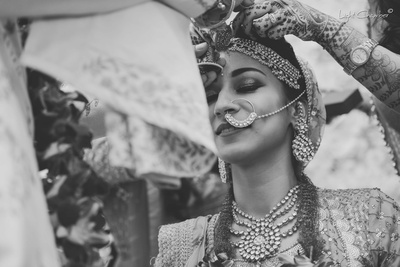 Black and white capture of the groom putting sindoor on the bride