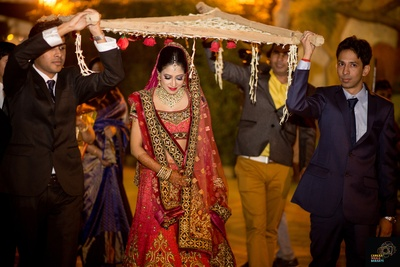 Red and green bridal lehenga by Tarun Tahiliani adorned with gold zardozi motifs and styled with kundan studded bridal necklace set