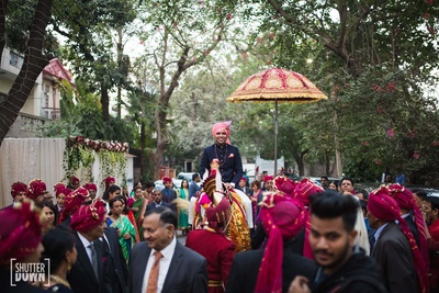 Traditional groom on ghodi as the baraat progresses